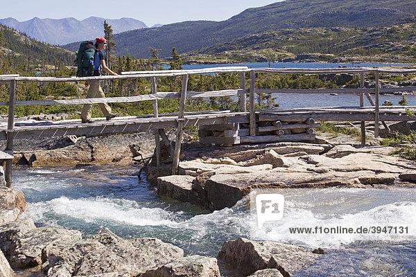 Junge Wanderin mit Rucksack überquert einen Bach auf einer Holzbrücke  dahinter der See Deep Lake  historischer Chilkoot Pfad  Chilkoot Pass  alpine Tundra  Yukon Territory  British Columbia  B.C.  Kanada