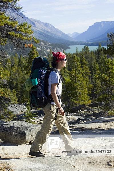 Junge Wanderin mit Rucksack  historischer Chilkoot Pfad  Chilkoot Pass  dahinter der See Lake Bennett  Yukon Territory  British Columbia  B.C.  Kanada