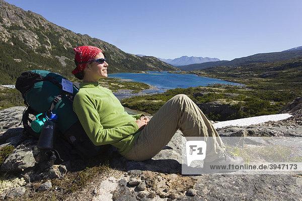 Junge Wanderin  Rucksacktourist  auf einem Felsen sitzend  ruht aus und genießt das Panorama  Deep Lake See  historischer Chilkoot Pass  Chilkoot Trail Wanderweg  Yukon Territory  British Columbia  BC  Kanada