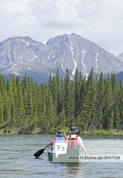 Paar  Mann und Frau beim Kanufahren  Paddeln auf dem oberen Liard River Fluss  dahinter die Pelly Mountains Berge  Yukon Territory  Kanada