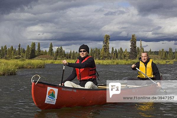 Paar  Mann und Frau paddeln im Kanu  Kanufahrt auf den Caribou Lakes Seen  dahinter Wolken  oberer Liard River Fluss  Yukon Territory  Kanada