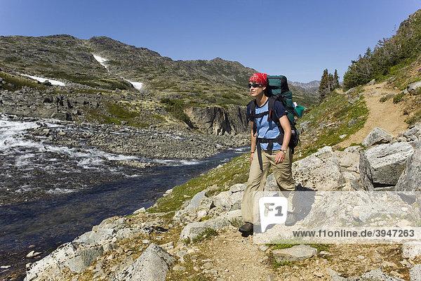 Junge Wanderin  Rucksacktourist  historischer Chilkoot Pass  Chilkoot Trail Wanderweg  dahinter ein Bach  alpine Tundra  Yukon Territory  British Columbia  BC  Kanada