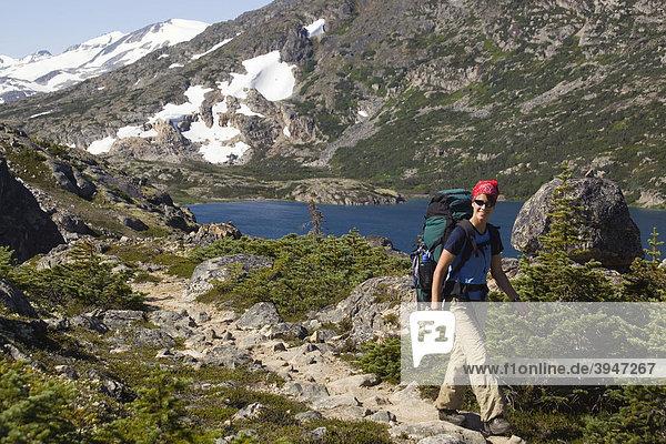 Junge Wanderin  Rucksacktourist  blühenden alpine Blumen  historischer Chilkoot Pass  Chilkoot Trail Wanderweg  dahinter der Long Lake See  alpine Tundra  Yukon Territory  British Columbia  BC  Kanada