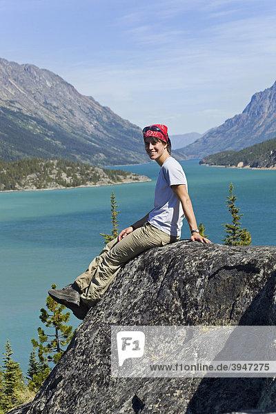 Junge Wanderin  Rucksacktourist  Rast  sitzt auf einem Felsen  geniesst das Panorama über dem Lake Bennett See  historischer Chilkoot Pass  Chilkoot Trail Wanderweg  Yukon Territory  British Columbia  BC  Kanada