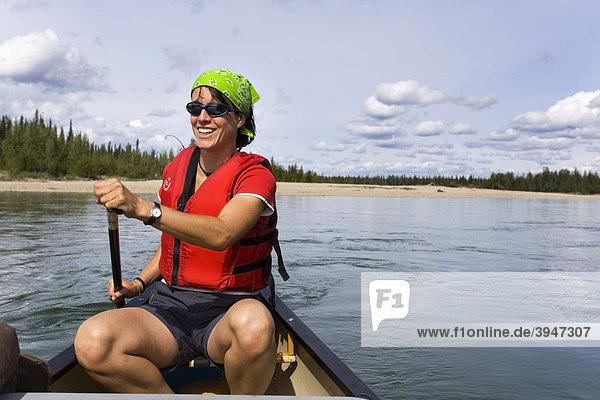 Junge Frau paddelt in einem Kajak  Lenken eines Kanus  oberer Liard River  Yukon Territory  Kanada