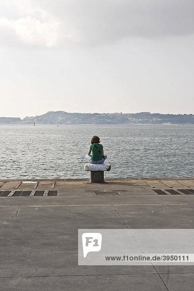 Eine Frau sitzt auf einem Poller und schaut aufs Meer im Hafen von Pozzuoli  Neapel  Kampanien  Italien  Europa