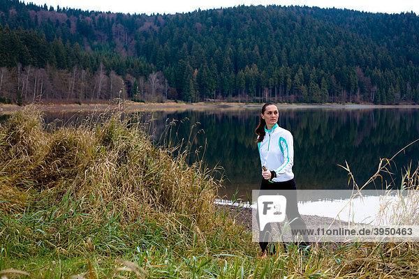 Junge Frau wandert am See im Nordic Walking Stil