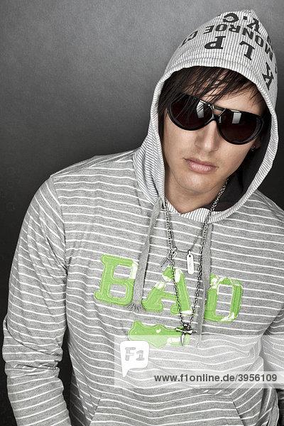 Junger Mann  Kapuzenshirt  Sonnenbrille  Portrait