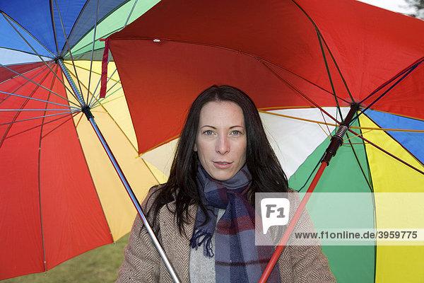 Junge Frau  30-35 Jahre  schützt sich mit zwei bunten Regenschirmen vor dem nasskaltem Winterwetter