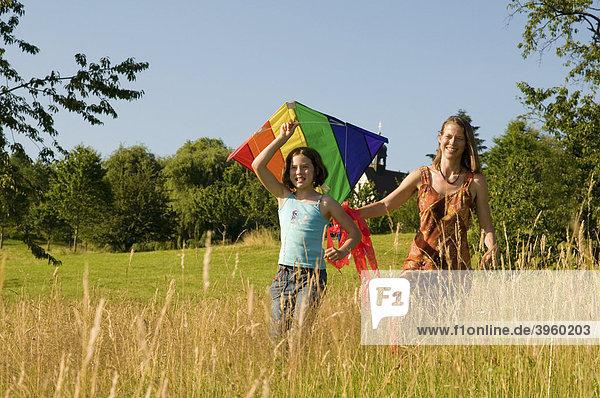 Junge Frau und Kind laufen mit einem Lenkdrachen über eine Wiese  Schwarzwald  Baden-Württemberg  Deutschland