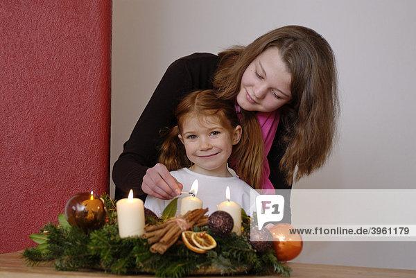 Junge Frau mit Kind zündet Kerzen an einem Adventskranz an