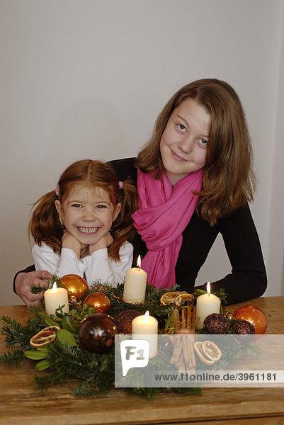 Junge Frau mit Kind sitzt vor einem Adventskranz