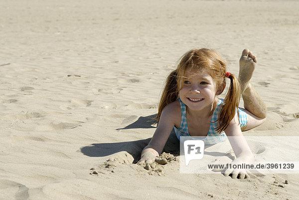 Mädchen liegt im Sand am Strand am Meer  Bibione  Adria  Venetien  Veneto  Italien  Europa