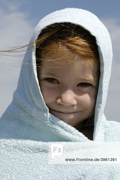 Girl wrapped in a towel after swimming