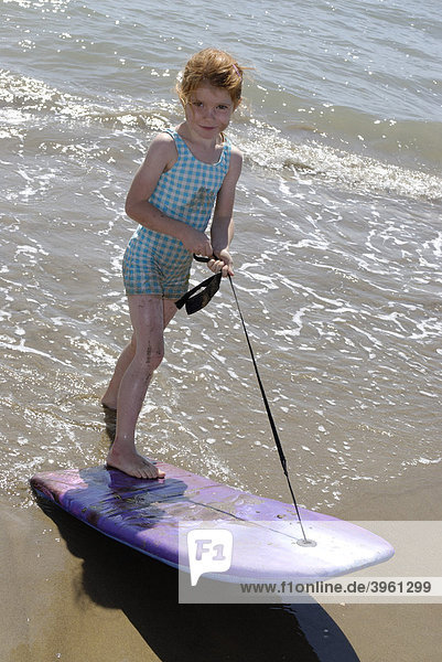 Kind mit Surfboard  Boogyboard  am Strand am Meer