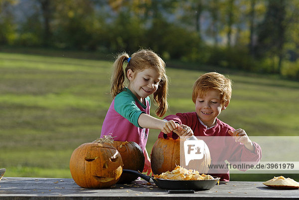 Zwei Kinder beim Kürbiskopf schnitzen für Halloween Herbstdekoration
