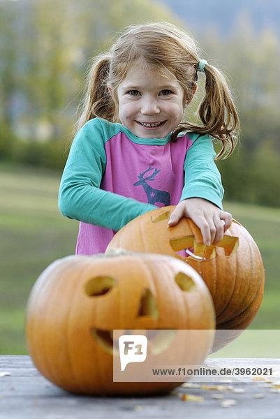 Mädchen schnitzt an einem Kürbis  Kürbiskopf  Kürbislaterne  für Halloween