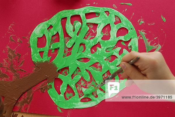Kinderhände beim Malen eines Baumes