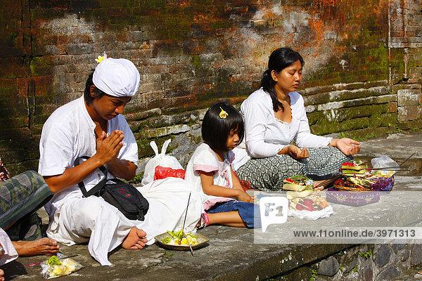 Betende Familie an einer heiligen Quelle  Tirta Empul  bei Tampak Siring  im Morgenlicht  Bali  Republik Indonesien  Südostasien
