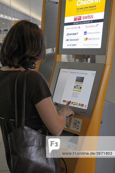 Frau steht vor einem Check-In-Terminal  Flughafen München  Oberbayern  Bayern  Deutschland  Europa