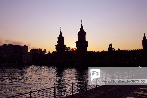 Silhouette of the Oberbaumbruecke bridge across the Spree river at sunset in Berlin  Germany  Europe