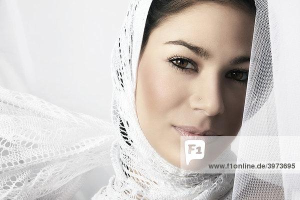 Portrait einer jungen dunkelhaarigen Frau mit Kopftuch  eingehüllt in ein weißes Tuch mit Blick zum Betrachter