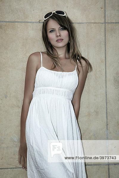 Portrait einer jungen dunkelblonden Frau im weißen Kleid und Sonnenbrille vor einer Wand aus Marmor