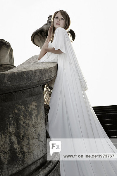 Fashion photo of a young dark blonde woman in a white dress with long train leaning on the railings of the Alexander Bridge  Paris  France  Europe