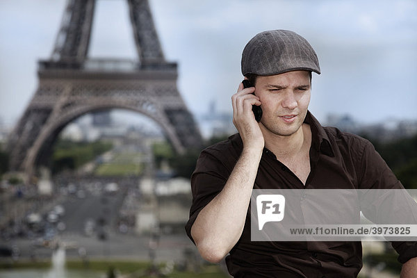 Young man on his mobile phone  the Eiffel Tower  Paris  France  Europe