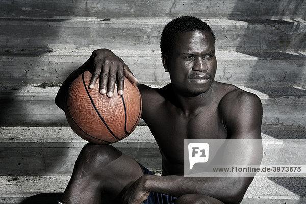 Dark-skinned basketball player sitting on stairs  portrait
