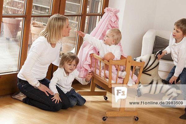 Mutter mit drei Kindern  1  3 und 6 Jahre  spielen mit Puppenwagen