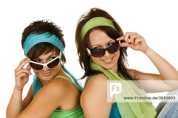 Two young women with sunglasses sitting back to back
