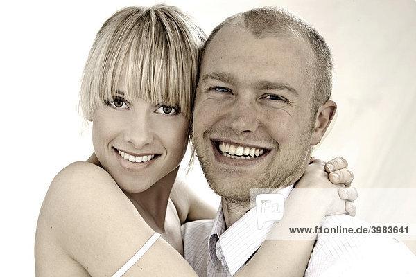 Junges Paar in weißer Kleidung  umarmt sich