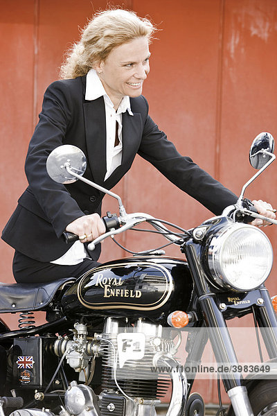 Frau im Business-Outfit mit Oldtimer-Motorrad