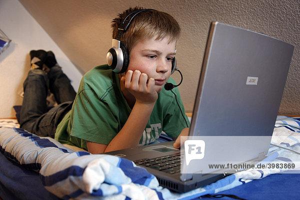Junge  13 Jahre alt  arbeitet mit seinem Computer zuhause in seinem Kinderzimmer auf dem Bett  surft im Internet auf einer Chat-Seite  spricht mit anderen Chat-Teilnehmern über sein Headset
