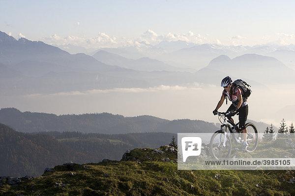 Mountain bike rider,  female,  on Hochries Mountain,  in front of Wilder Kaiser Mountain,  Chiemgau Alps,  Bavaria,  Germany