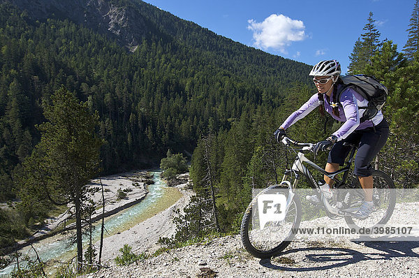 Female mountainbike rider beside the Isar River  southeast of Scharnitz  Tyrol  Austria  Europe