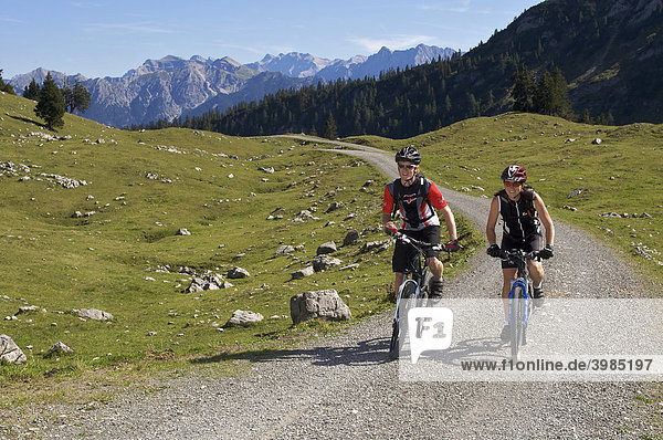 Mountainbike-Fahrerin und -Fahrer unterhalb der Kuhalm  Eschenlohe  Oberbayern  Bayern  Deutschland