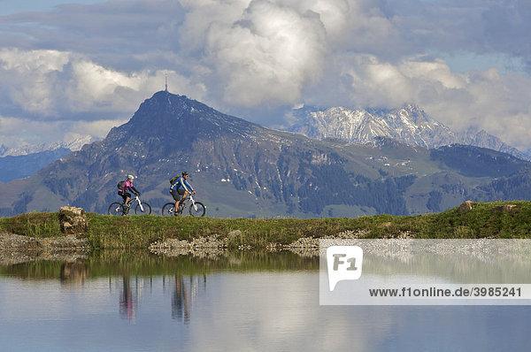 Mountainbike-Fahrerin und -Fahrer spiegeln sich im Wasserreservoir Salvensee an der Hohen Salve  dahinter Kitzbüheler Horn  Tirol  Österreich