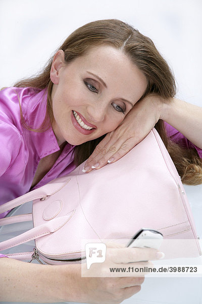 Frau in pinker Bluse mit Handy