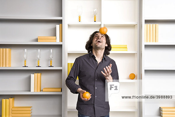 Young man juggling in front of a shelf in a flat