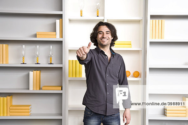 Young man standing in front of shelf in a flat  thumbs up