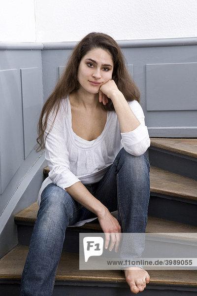 Mädchen sitzt gelangweilt auf alter Holztreppe