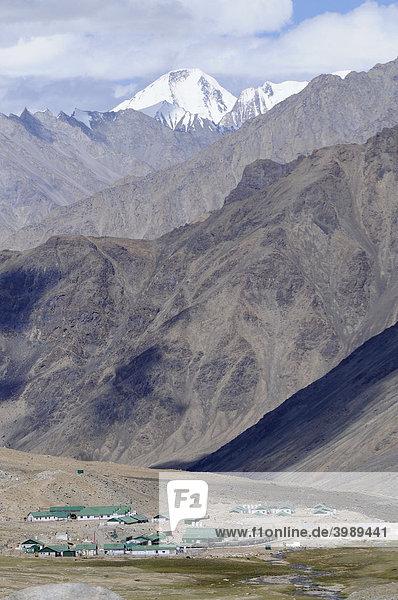 Militärlager und Kontrollpunkt North Pullu am Khardong-Pass Richtung chinesisch-pakistanisch-indisches Grenzgebiet  mit Karakorumgebirge am Horizont  Nubratal  Ladakh  Jammu und Kashmir  Nordindien  Himalaja  Asien