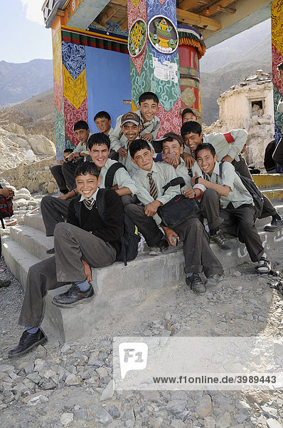 Students wearing uniforms in front of a prayer wheel in Hunder  Nubra Valley  India  the Himalayas
