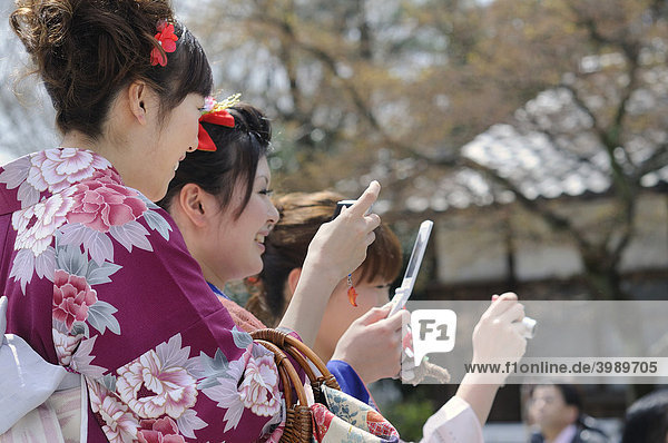 Young women in kimonos and with mobile phones in the old town  Kyoto  Japan  Asia