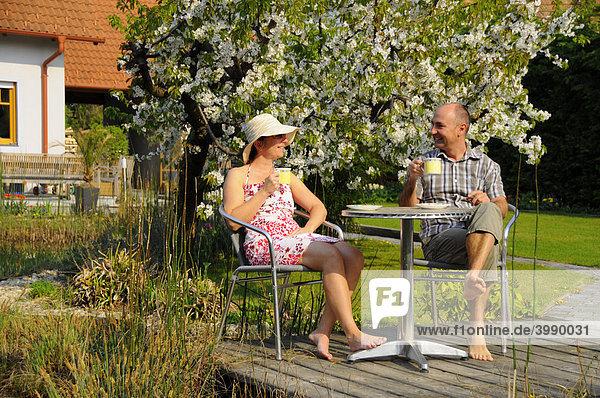 Paar beim Kaffeetrinken am Gartenteich vor blühendem Kirschbaum