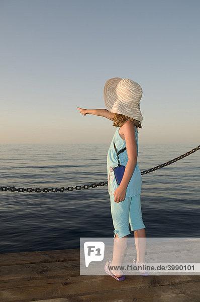 Achtjähriges Mädchen zeigt auf den Horizont