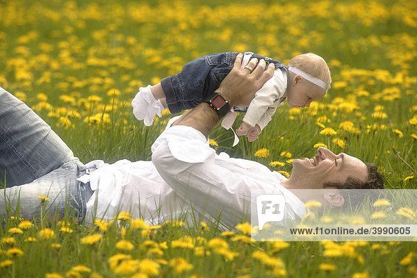 Vater mit Baby  Mädchen  in der Frühlingwiese