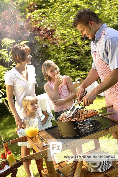 Familie beim Barbecue im Garten